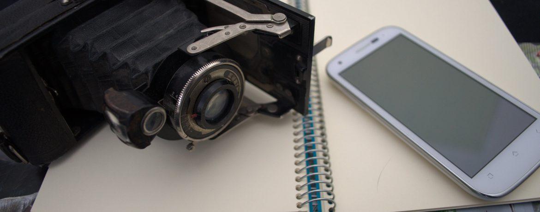 Photo d'un vieil appareil photo face à un téléphone portable, sur un cahier pour l'atelier Roman-photo